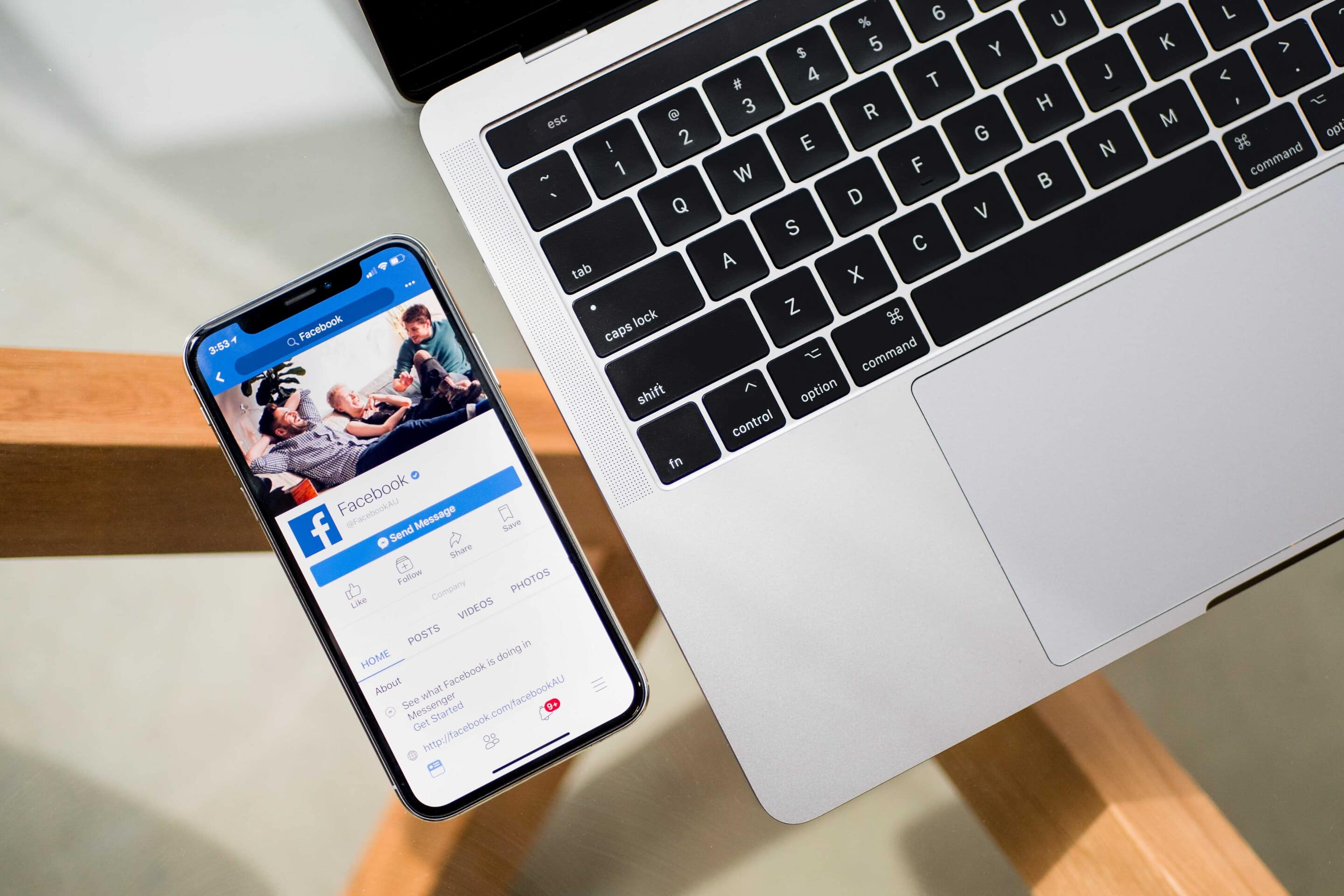 Table with an Apple Mac and phone placed on it. The phone shows a Facebook page on the screen.